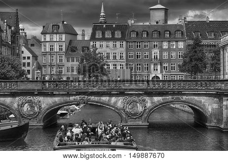COPENHAGEN DENMARK - AUGUST 14 2016: Black and white photo view of canal boat with tourist and old bridge from bridge Prinsens Bro in Copenhagen Denmark on August 14 2016.