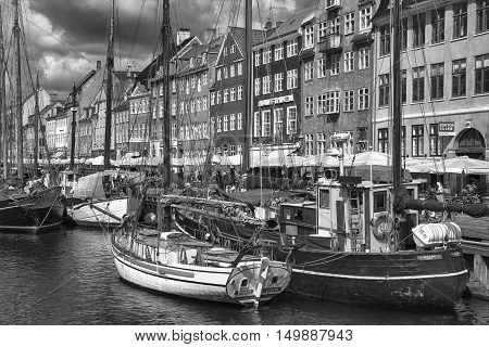 COPENHAGEN DENMARK - AUGUST 14 2016: Black and white photo boats in the docks Nyhavn people and colorful architecture. Nyhavn a 17th century harbour in Copenhagen Denmark on August 14 2016.