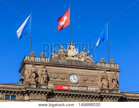 Zurich, Switzerland - 25 September, 2016: upper part of the Zurich Main Railway station building with sculptures and flags. Zurich Main Railway station is the largest railway station in Switzerland.