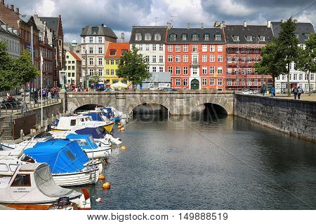 COPENHAGEN DENMARK - AUGUST 14 2016: View of canal boat with tourist and old bridge from bridge Marmorbroen in Copenhagen Denmark on August 14 2016.