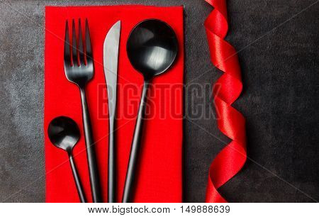 Steel black cutlery set - knife, spoon, fork, tea spoon on red napkin. Black background. Free space for text. Copy space. Top view