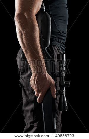 close-up of strong man in black military uniform holding sniper rifle isolated on black background