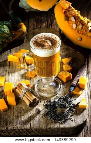 Pumpkin tea. Cup of autumm hot drink - pumpkin tea with milk cream and cinnamon and ingredients - fresh pumpkin, tea, cinnamon, nutmeg. Wooden rustic background