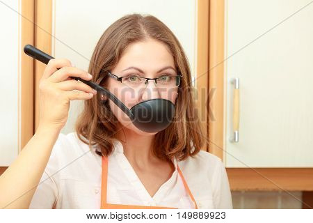 Housewife tasting soup meal dinner. Middle aged woman holding spoon ladle. Housekeeper preparing food.