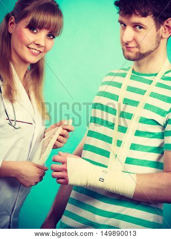 Healthcare and protection. Young man with broken hand sprained wrist visit female doctor. Specialist with bandage.