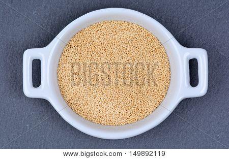 Amaranth seeds in a ceramic bowl on slate