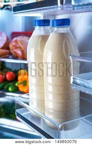 Products in the refrigerator. Bottles of milk in the fridge