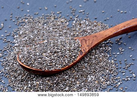 Chia seeds in a wooden spoon on slate