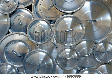 Pile of aluminum pan caps of several sizes forming a background