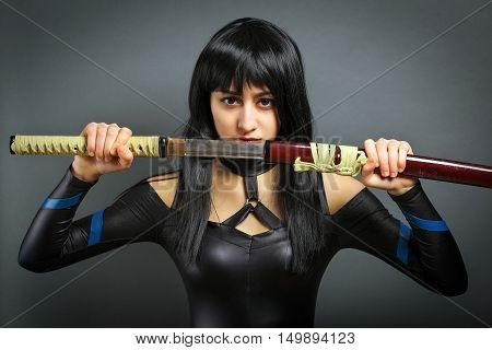 Beautiful girl with sword on grey background. She pulls out the sword