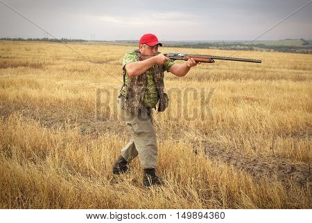 Hunter with a gun on the field aiming at the prey