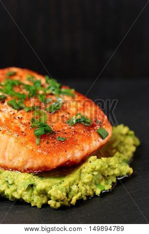 Grilled salmon fillet with avocado mash on black slate plate