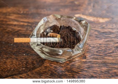 Cigarette butts with ash in ashtray on wooden table