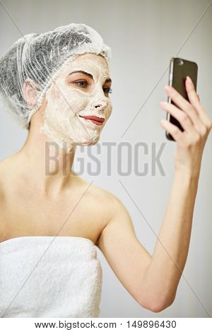 Portrait of smiling woman with cosmetic mask on face and mesh hair cap on head with phone in hand.