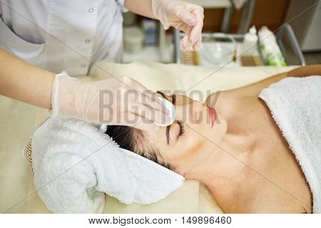 Beautician hands in rubber gloves wipe with cotton pad forehead of woman covered by towel that lies on couch in beauty salon.