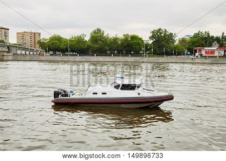Patrol boat on river in city on summer day.