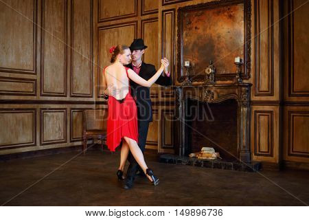 Handsome girl and man in hat dancing tango in retro room with fireplace