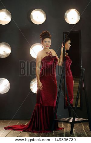 Pretty brunette woman in red long dress poses near mirror in studio with lamps on wall