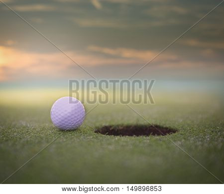 Golf ball sitting on a golf course putting green next to the hole. with a beautiful sunset.