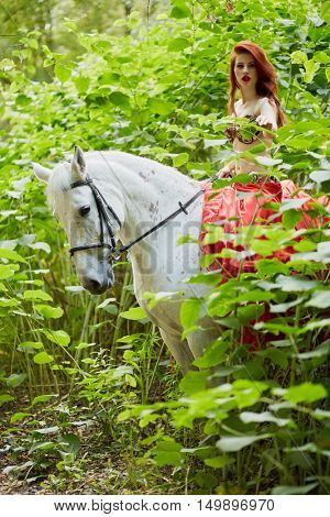 Red-haired young woman in red dress sits on white horse among green plants in park.