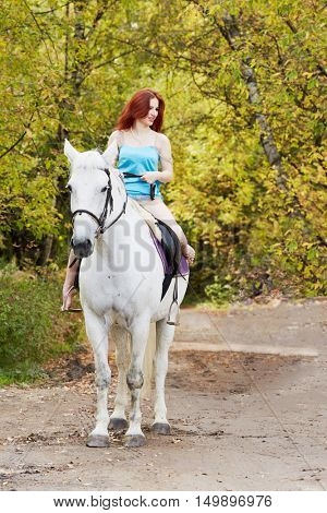 Young smiling red-haired woman rides on white horse in park.