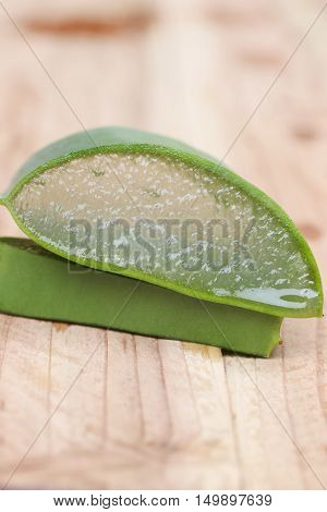 aloe vera slice on wooden floor and can you see texture of aloe vera gel.