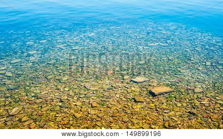 Transparent shallow water with rocky bottom fading away to deeper water at top.
