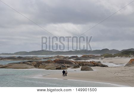 DENMARK,WA,AUSTRALIA-OCTOBER 2,2014: Old couple taking a walk on the beach at Green's Pool under stormy skies with granite rock formations in Denmark, Western Australia.
