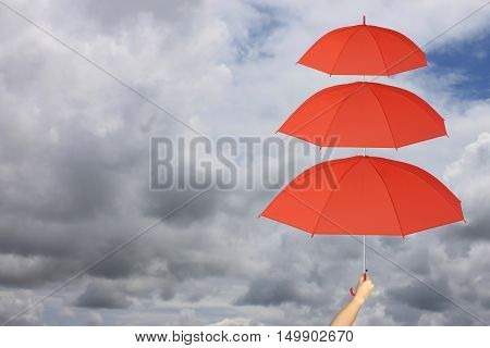 Red umbrella third layers in hand and rain protection more thanconcept for management business idea on rain cloud background.