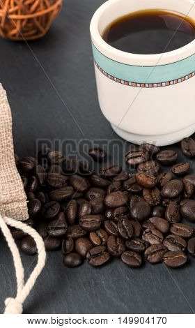 Heap coffe beans and cup of fresh coffee on dark background