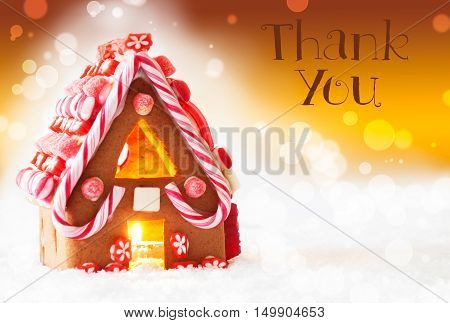 Gingerbread House In Snowy Scenery As Christmas Decoration. Candlelight For Romantic Atmosphere. Golden Background With Bokeh Effect. English Text Thank You