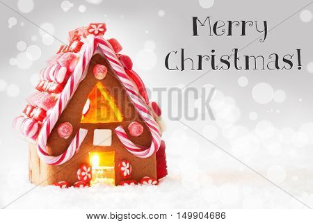 Gingerbread House In Snowy Scenery As Christmas Decoration. Candlelight For Romantic Atmosphere. Silver Background With Bokeh Effect. English Text Merry Christmas
