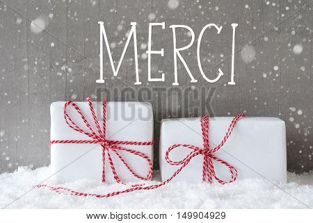 French Text Merci Means Thank You. Two White Christmas Gifts Or Presents On Snow. Cement Wall As Background With Snowflakes. Modern And Urban Style.