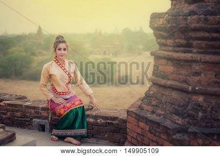 Beautiful girl in Myanmar traditional costume identity culture of Myanmar Pagdodas of Bagan Background Happy asian woman