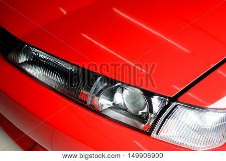 Car detailing series : Closeup of clean red car headlight