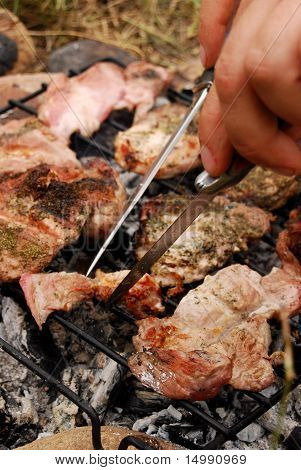 Male arranging pork on a barbecue