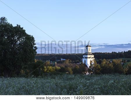 A church in a village, farmland this side. Summer and sunshine. Buildings among the vegetation.