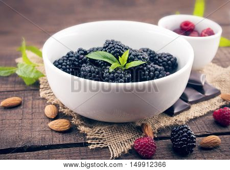Close Up Of Ripe Blackberries In A White Ceramic Bowl Over Rustic Wooden Background. Ingredients For