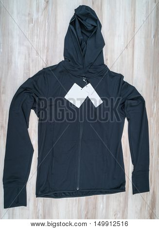 Long Black Jacket with price tag on  wooden background