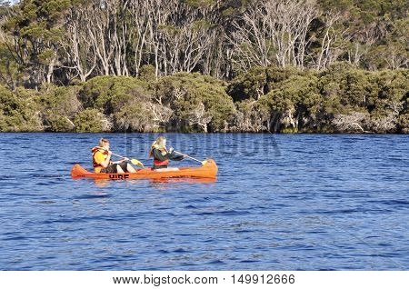 WALPOLE,WA,AUSTRALIA-OCTOBER 3,2014: Tourists canoeing on the Walpole River with lush forest border in Walpole, Western Australia.