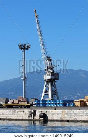 Grey shipyard loading crane standing on edge of the pier and next to tall light tower