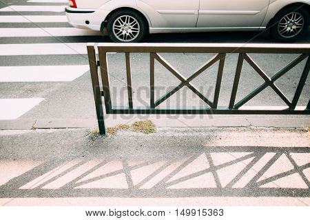Steel fence near pedestrian zebra, going car on background. Close-up of metal barricade separating road and sidewalk, safety in city concept