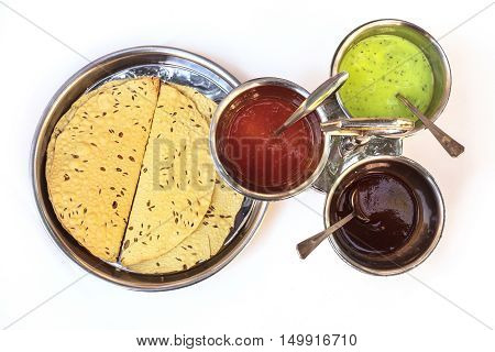 Indian bread served with the traditional assortment of sauces, in the typical tableware. Shot from above on white background