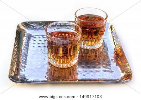 A photo of two glasses of Pacharan, typical sloe flavored Spanish liquor, on a tray, isolated on white