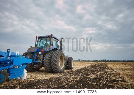 The tractor wheels on the huge field, a farmer riding a tractor, a tractor working in a field agricultural machinery in the work, tractor in the background cloudy sky
