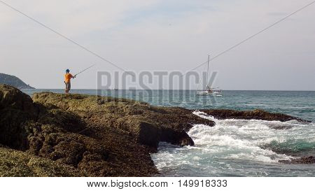 a Landscape view of sea with fisherman standing on rock southern of Thailand on Phuket Island