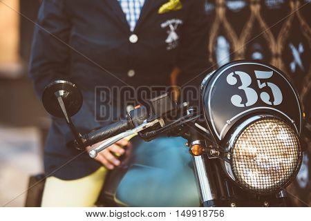 Focus on bike number above headlight over unfocused man sitting on it