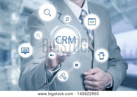 business, technology, internet and customer relationship management concept. Businessman pressing crm button on virtual screens.