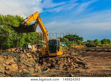 excavator yellow. on a construction site against blue sky