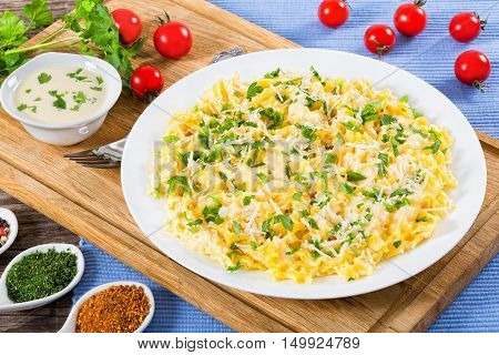 Fettuccine Alfredo served in a sauce of cream butter and grated Parmesan cheese sprinkled with parsley on white dish on cutting board view from above close-up